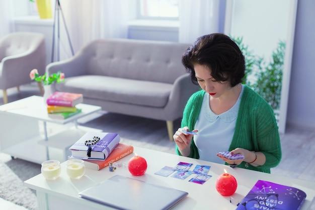 Wróżenie z kart tarota. dobrze wyglądająca inteligentna kobieta, otwierająca karty tarota, przepowiadająca przyszłość