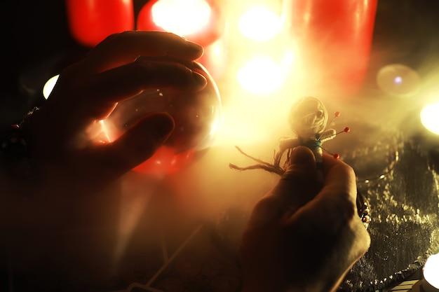 Wróżka przyszłości. mistyczna martwa natura z lalką voodoo, kartami tarota, książkami, złymi świecami i przedmiotami czarów. rytuał wróżbiarski.