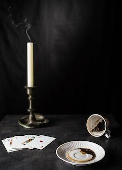Wróżki czytające fusy z kawy w stanie znajdują się w pobliżu talii kart i świecy w starym świeczniku