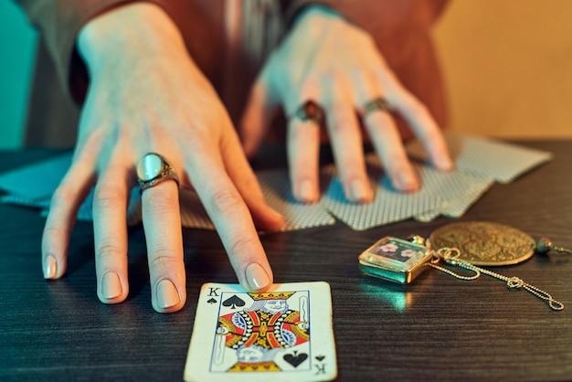 Wróżki ręce z biżuterią przedstawiającą karty do gry