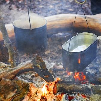 Wrząca woda w dwóch garnkach nad ogniem