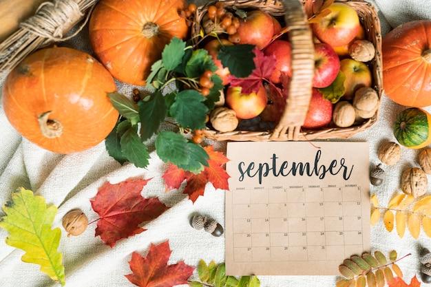 Wrześniowe zbiory dojrzałych jabłek i orzechów włoskich w koszu, dynie, żołędzie i liście w pobliżu, tworząc jesienną kompozycję