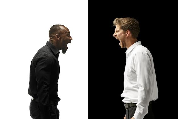 Wrzeszczący afro i kaukaski mężczyźni. para mieszana. dynamiczny obraz męskich modeli na białym i czarnym studio. koncepcja ludzkich emocji twarzy.
