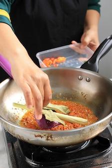 Wrzuć suszony liść laurowy (daun salam) na patelnię z pikantnymi przyprawami, gotując krok po kroku przez szefa kuchni w kuchni. proces wytwarzania indonezyjskiej tradycyjnej receptury o pikantnym smaku