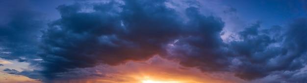 Wschód lub zachód słońca po burzy, jasna panorama dramatycznego nieba