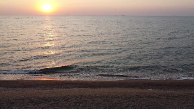 Wschód słońca i fale na morzu, widok z piaszczystej plaży.
