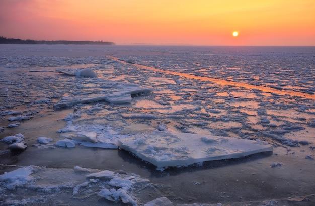 Wschód słońca i zamarznięte morze. piękny zimowy krajobraz z jeziorem w godzinach porannych.