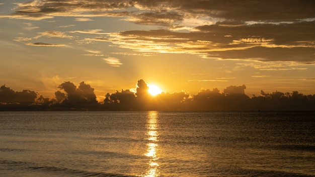 Wschód słońca kręcił się nad morzem i piękną chmurą. słońce zniknęło za wielką chmurą nad oceanem.