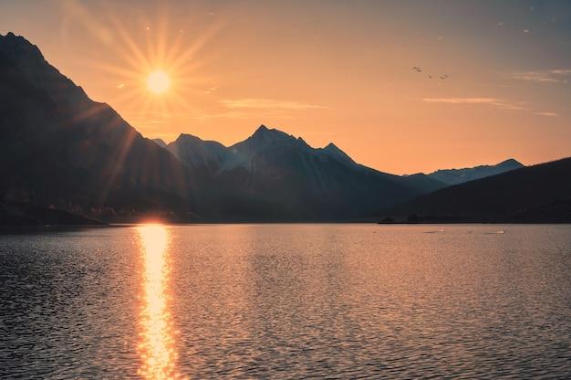 Wschód słońca na kanadyjskich skałach skalistych z kolorowym niebem nad jeziorem medicine w parku narodowym jasper, kanada