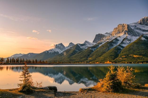 Wschód słońca na mount rundle z odbiciem błękitnego nieba nad zbiornikiem rundle forebay jesienią w canmore, kanada