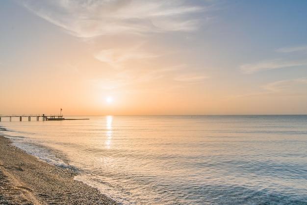 Wschód słońca na plaży. spokojne morze bez fal rano.