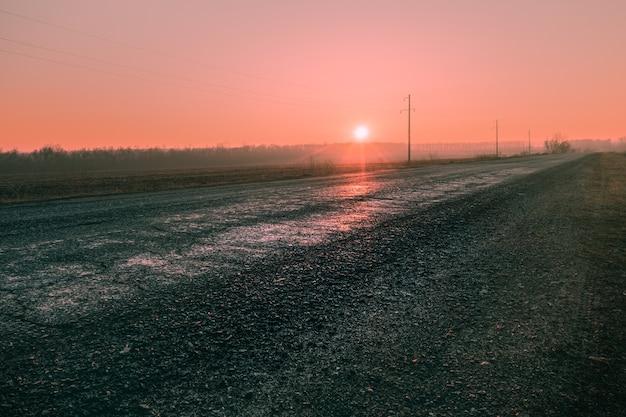 Wschód słońca na różowym niebie wczesnym rankiem na wiejskiej drodze. poranne słońce wschodzi nad horyzont wczesnym rankiem nowego dnia.