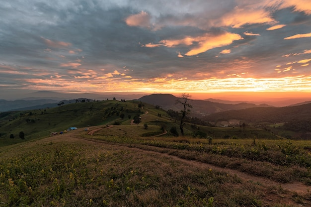 Wschód słońca na wzgórzu pola uprawnego z kolorowym niebem i turystów na wakacjach w parku narodowym w doi mae tho w chiang mai