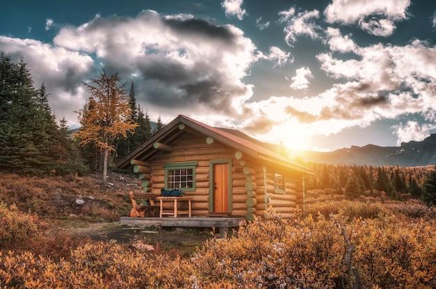 Wschód słońca nad drewnianą chatą w jesiennym lesie w parku prowincjonalnym assiniboine, kanada