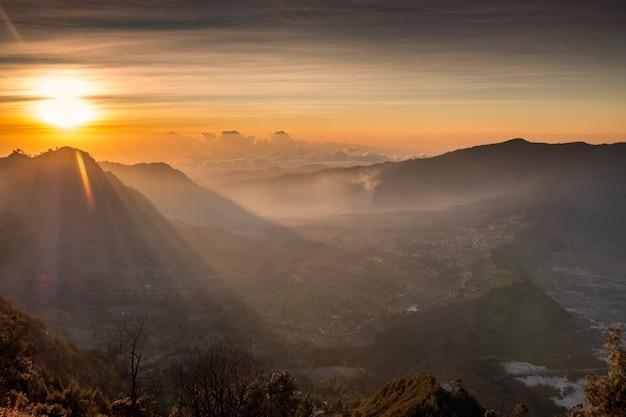 Wschód słońca nad górą z mgłą z wioską na wzgórzu o poranku