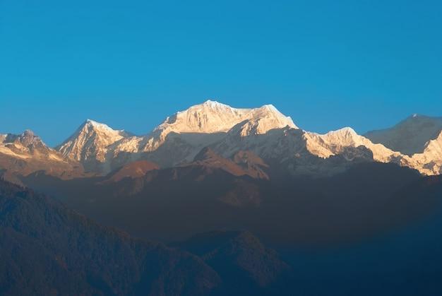 Wschód słońca nad kangchenjunga w indiach. śnieżne duże góry z niebieskim niebem.