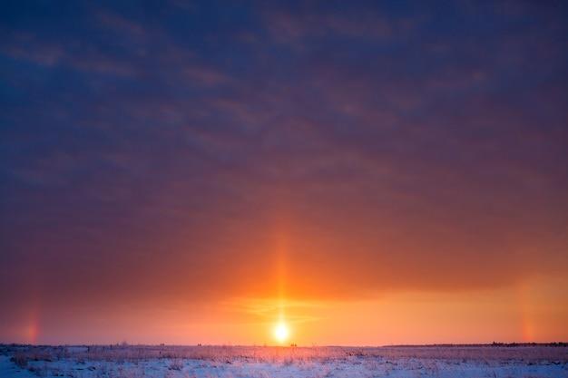 Wschód słońca nad łąką zimą w silnym mrozie.