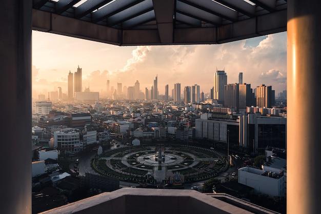 Wschód słońca nad miastem bangkok z pomnikiem ronda wongwianyai w dzielnicy biznesowej