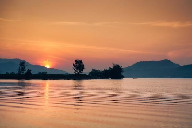 Wschód słońca nad pasmem górskim na zbiorniku lam taphoen w okolicy w suphanburi, tajlandia