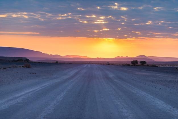 Wschód słońca nad pustynią namib, roadtrip w cudownym namib naukluft parku narodowym, podróży miejsce przeznaczenia w namibia, afryka. poranne światło, mgła i mgła, przygoda poza drogą.