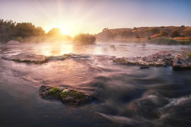 Wschód słońca nad rwącą rzeką
