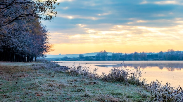 Wschód słońca nad rzeką w mroźny poranek. rano pokryte szronem drzewa i trawa na brzegu rzeki
