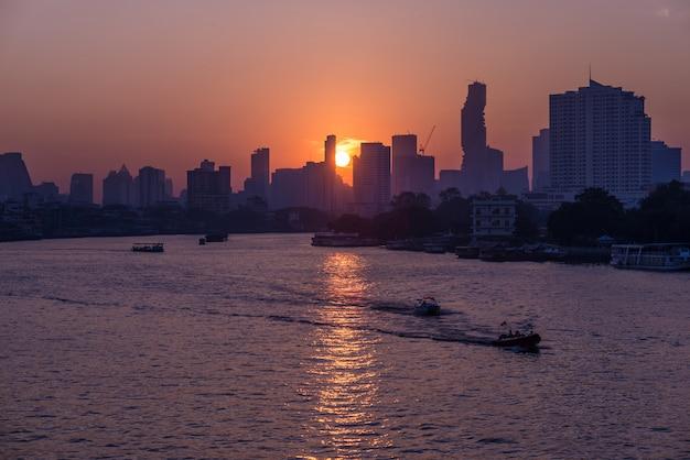 Wschód słońca nad sceniczną linią horyzontu przy bangkok, tajlandia, przeglądać w backlight przy wschodem słońca z pomarańczowym czerwieni jasnego niebem.