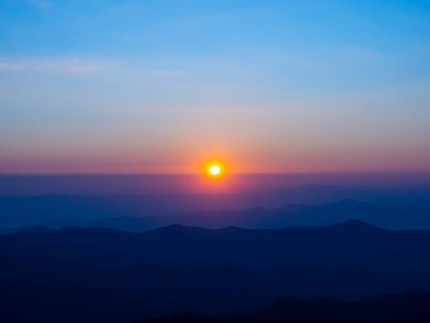 Wschód słońca o poranku to czerwono-pomarańczowy okrąg na linii horyzontu