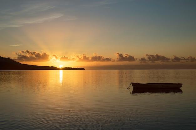 Wschód słońca w mauritiusie z słońcem w tle i łodzią rybacką na przedpolu