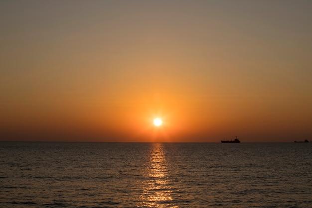 Wschód słońca z pomarańczowym i żółtym tłem nieba i krajobrazu