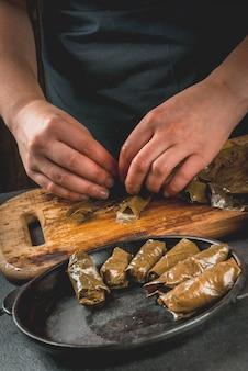 Wschodnia armeńska, tradycyjna turecka żywność narodowa wegańskie jedzenie. osoba w ramce przygotowuje mięso dolma z warzywami, owinięte liśćmi winogron. domowe jedzenie. kobiece ręce