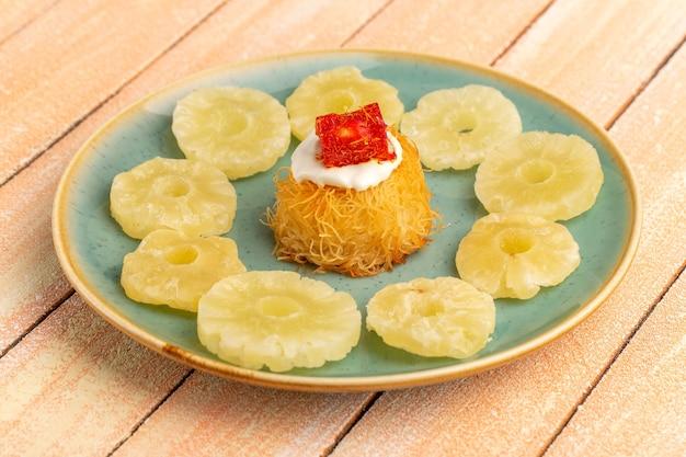 Wschodnie ciasteczka ciasteczka wewnątrz talerza z białymi kremowymi suszonymi pierścieniami ananasa na drewnianym stole