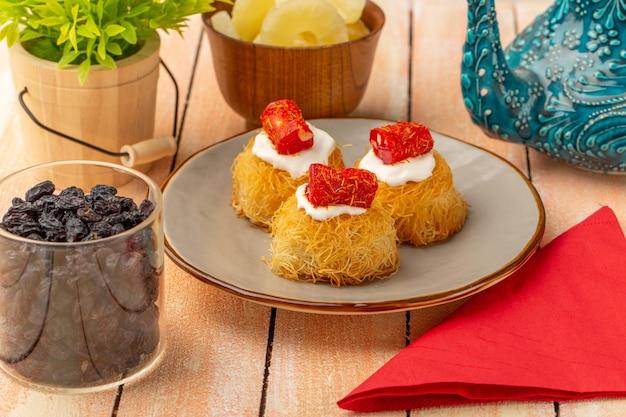 Wschodnie ciasteczka wewnątrz talerza z białą śmietaną wraz z suszonymi krążkami ananasa, suszonymi owocami