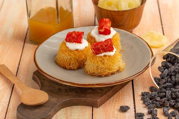 Wschodnie ciasteczka z ciasta z białym kremem suszonym ananasem i suszonymi owocami na drewnianym stole