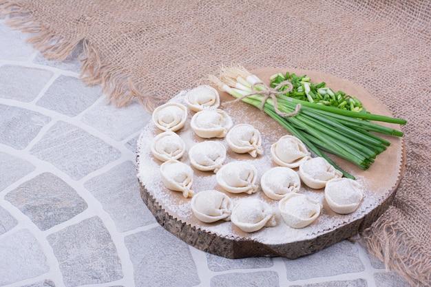 Wschodnie ciasto chinkalowe z mielonymi ziołami i pęczkiem cebuli na desce.