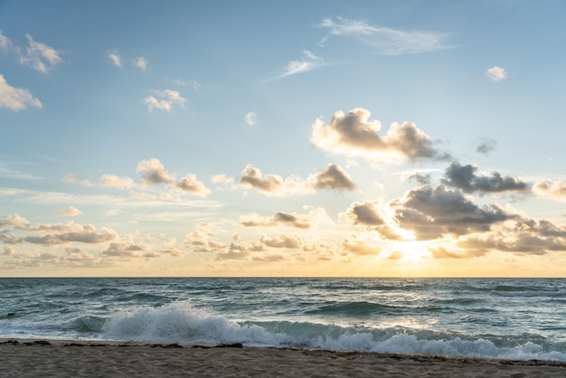 Wschodzące słońce na horyzoncie nad oceanem lub morzem. na niebieskim niebie białe chmury