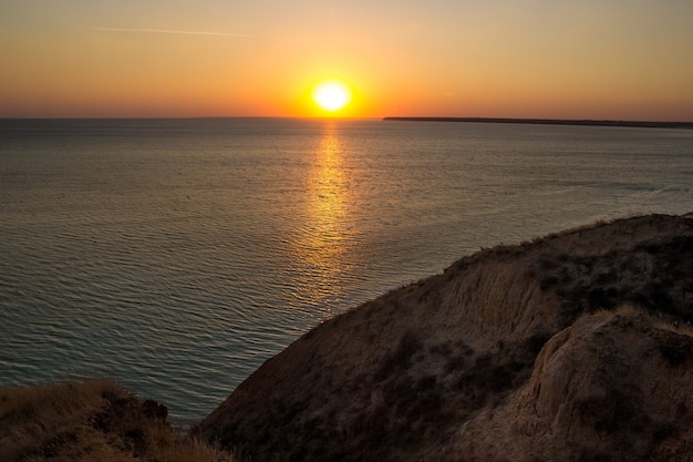 Wschodzące słońce odbijające się w wodzie spokojnymi falami oceanu.