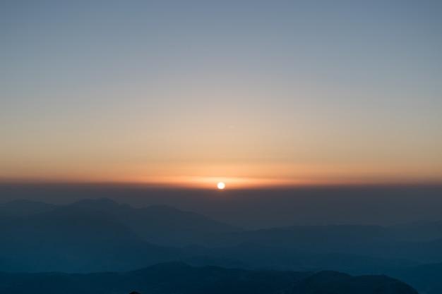Wschodzące słońce wschodzi z odległego horyzontu