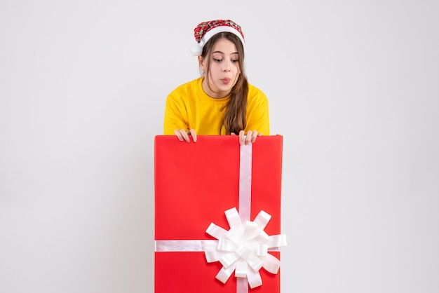 Wścibska dziewczyna z santa hat patrząc w dół stojący za wielkim prezentem świątecznym na białym tle