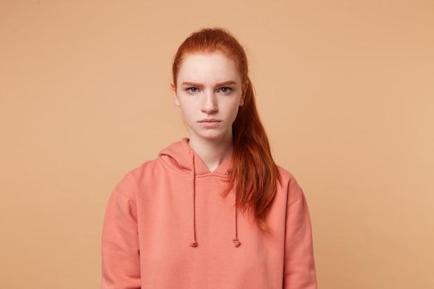 Wściekła, gburowata rudowłosa kobieta z ogonem i zimnymi niebieskimi oczami wygląda na niezadowoloną