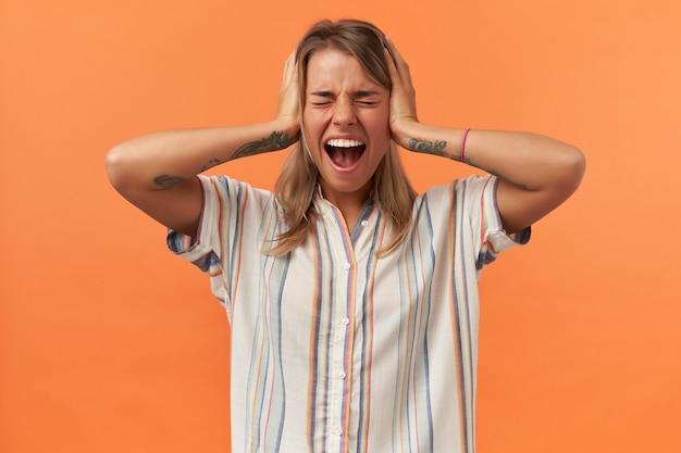 Wściekła histeryczna młoda kobieta w zwykłych ubraniach ma zamknięte oczy, zakryte uszy dłońmi i krzyczy na białym tle nad pomarańczową ścianą