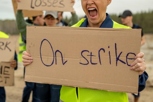 Wściekła kobieta konstruktorka krzyczy, niosąc afisz podczas strajku