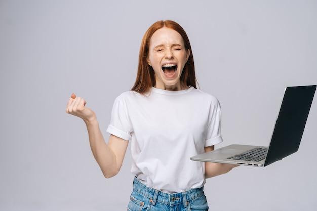 Wściekła krzycząca młoda biznesowa kobieta lub studentka z otwartymi ustami trzymająca laptopa
