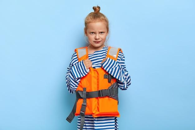 Wściekła mała dziewczynka z rudymi włosami odpoczywa podczas letnich wakacji, nosi za duży sweter w paski, a niezadowoleni rodzice nie pozwalają jej pływać samotnie z przyrządem pływackim. dziewczyna w kamizelce ratunkowej