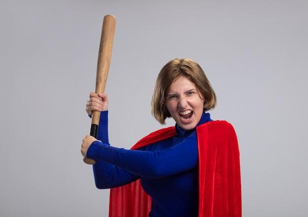 Wściekła młoda blond superbohaterka w czerwonej pelerynie stojąca w widoku profilu trzymająca kij baseballowy, przygotowująca się do uderzenia z krzykiem na białej ścianie z miejscem na kopię