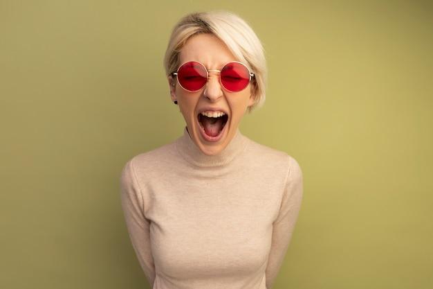 Wściekła młoda blondynka w okularach przeciwsłonecznych trzymająca ręce za plecami, wyglądająca krzycząc, odizolowana na oliwkowozielonej ścianie z miejscem na kopię