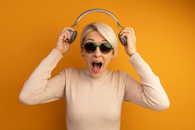 Wściekła młoda blondynka w okularach przeciwsłonecznych, zdejmująca słuchawki z krzykiem