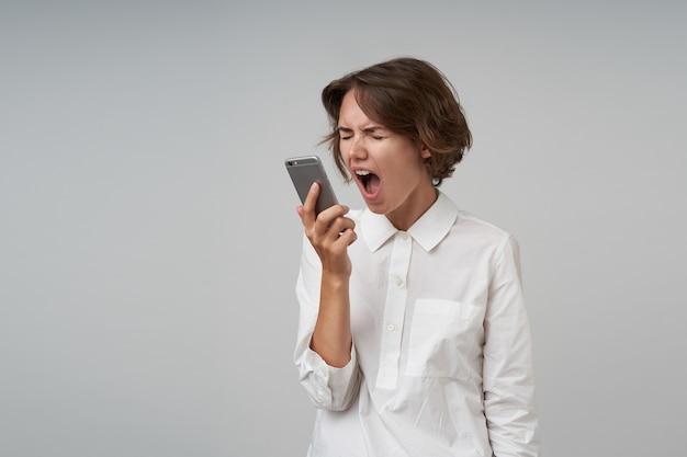 Wściekła młoda brunetka z przypadkową fryzurą krzyczy głośno do słuchawki z szeroko otwartymi ustami, trzymając oczy zamknięte, ubrana w białą koszulę podczas pozowania