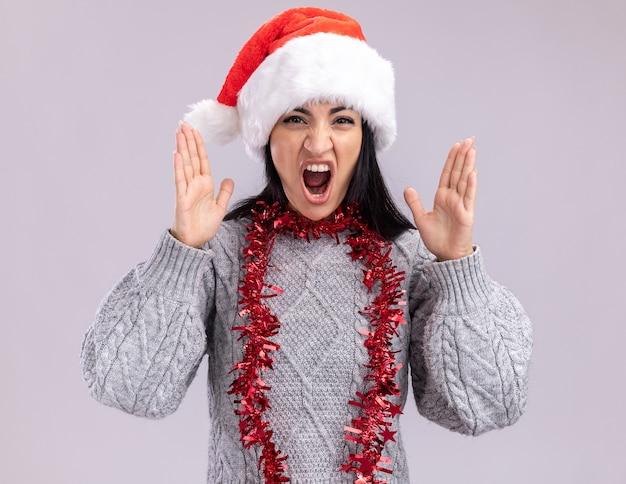 Wściekła młoda kaukaska dziewczyna ubrana w świąteczny kapelusz i świecącą girlandę wokół szyi, patrząc na kamerę, trzymając ręce w powietrzu krzycząc na białym tle