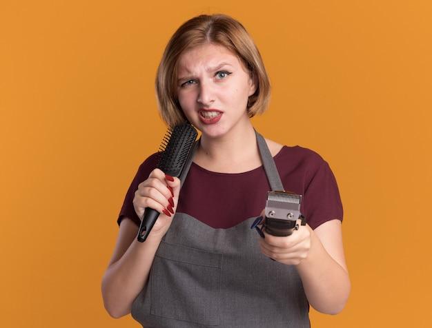 Wściekła młoda piękna kobieta fryzjerka w fartuchu trzymająca trymer i szczotkę do włosów patrząc z przodu niezadowolona stojąc nad pomarańczową ścianą